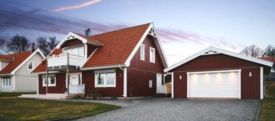 Garageport och garageuppfart till rött hus